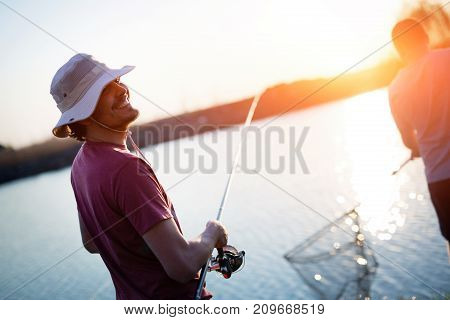 Young man fishing on a lake at sunset and enjoying hobby and recreation