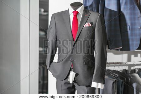 Male mannequin dressed in elegant suit at menswear store
