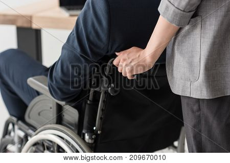 Businesswoman Helping Disabled Colleague