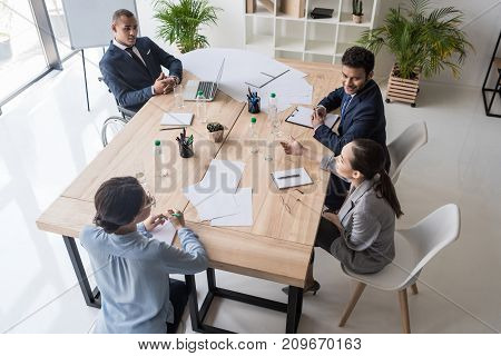 high angle view of multicultural businesspeople discussing new business strategy at workplace in office