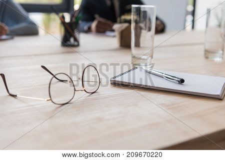close up view of eyeglasses notebook pen and glass of water at workplace in office