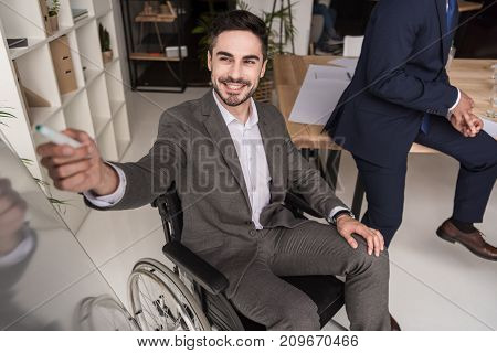 smiling disabled businessman in wheelchair pointing at whiteboard during business meeting with colleagues