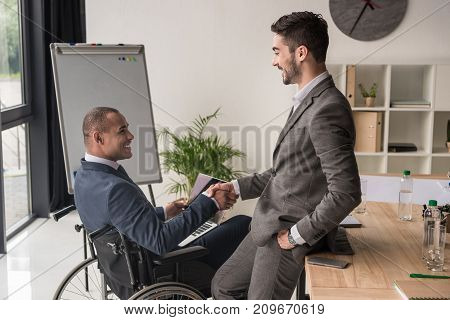 side view of smiling multiethnic businessmen shaking hands at workplace