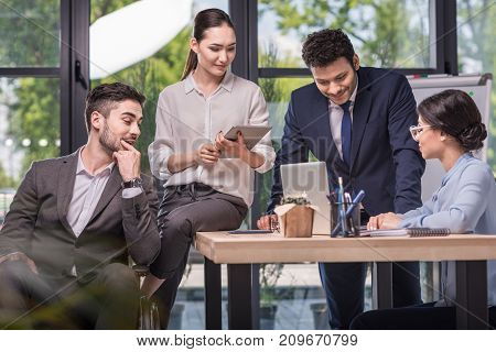 multicultural businesspeople with digital devices discussing business plan at workplace
