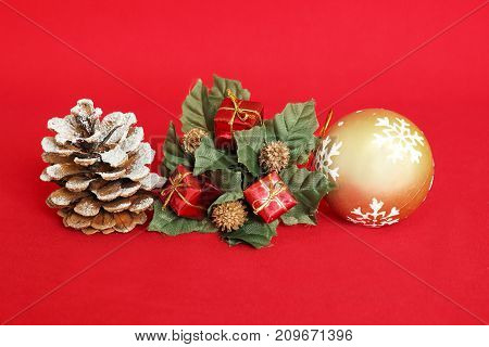 A pine apple with snow, red gifts and a golden ball on a red background for holiday decoration