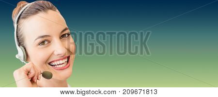 Portrait of cheerful woman wearing microphone headset against green and blue background