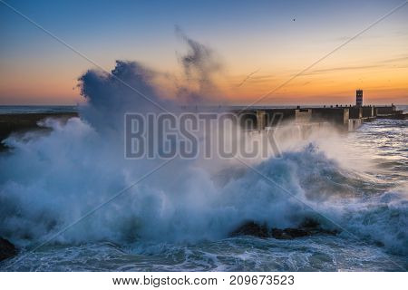 Large waves on Atlantic Ocean during sunset in Porto Portugal