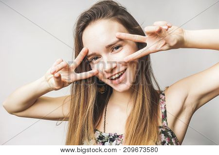 Funny woman shows two thumbs ,peace on a white background