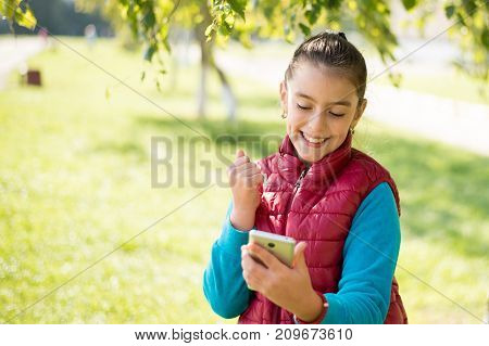 Beautiful girl talking on a smartphone in a red vest on the outdoor.Portrait smiles girl positive, emotion, happiness, smile. Young caucasian girl receiving good news by phone. Portrait smiles girl