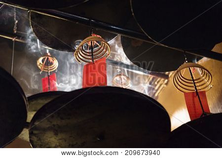 Incense spirals burning with red cards at the ceiling of Man Mo temple, Hong Kong, Asia