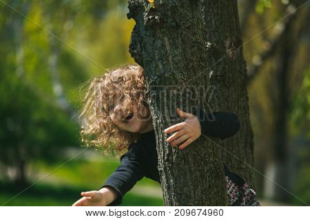The little girl climbed into a tree. The child is calling his mother. The family plays on the street. Children's health.
