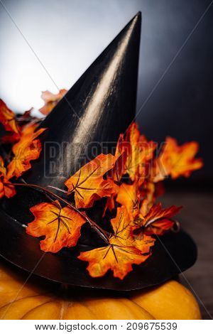 a composition for decorating a house for halloween, lie yellow and orange pumpkins, a large black witch hat decorated with autumn yellow leaves