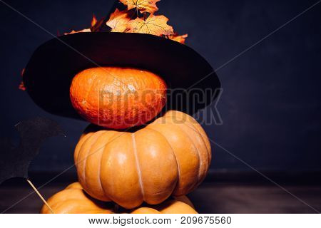 a composition for decorating a house for halloween, lie yellow and orange pumpkins, a large black witch hat decorated with yellow autumn leaves