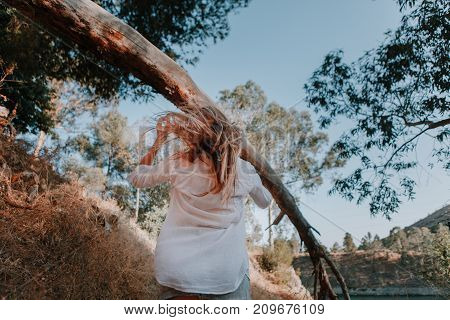 Woman with windy hair walking under a fallen tree in the forest