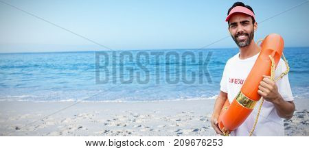 Portrait of male lifeguard holding life belt against beach against clear sky