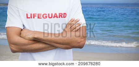 Mid section of male lifeguard against scenic view of beach