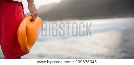 Cropped image of man holding rescue buoy against mountain against sky at beach