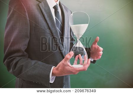 Mid section of businessman holding hourglass against green chalkboard