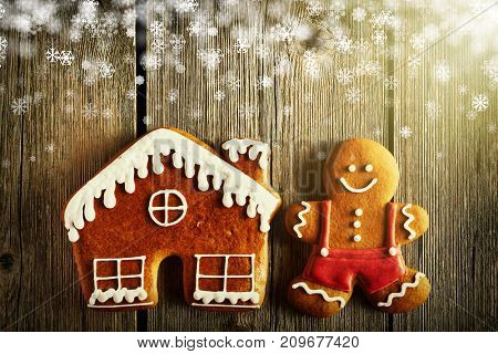 Christmas homemade gingerbread man and house on wooden table