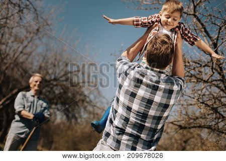 Three generations. Strong man standing with back on camera and looking upwards while raising his son