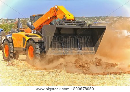 Yellow Tractor With A Bucket Demonstrates Work