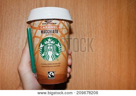 MOSCOW, RUSSIA - OCTOBER 9, 2017: Hand Holding Starbucks Coffee Take Away Cup. New format of Starbucks Coffee - company drinks selling at grocery shops. Wooden background.