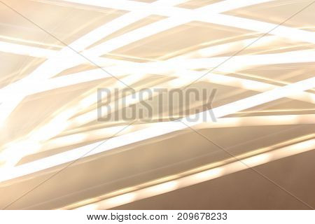 Bright Vivid Lights Pattern Abstract Defocused Background. Blurred bokeh picture of shiny golden and yellow colored glittering lines. Flaming vintage style effect creative picture for background.