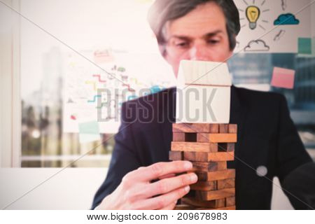 Businessman arranging wooden blocks at table against adhesive notes on window
