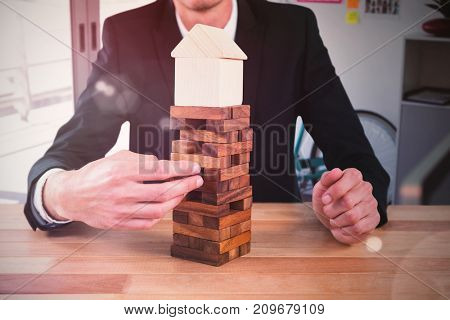 Businessman arranging blocks with model house on top against employee relaxing on table in creative office