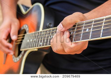 Close up guitar. Soft focus image of Man 's hand playing guitar sitting on green grass. Nature background. Music guitar and nature. Country folk song from acoustic guitar. Man holding his guitar