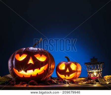 Grinning pumpkin lattern or jack-o'-lantern is one of the symbols of Halloween. Halloween attribute. Wooden background.