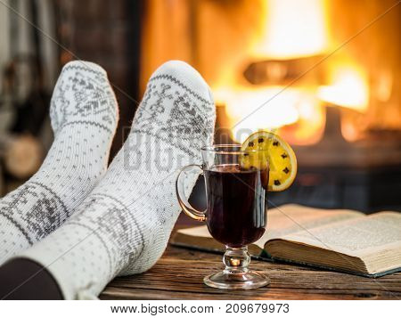 Warming and relaxing near fireplace. Woman feet near the cup of hot wine and a book in front of fire.