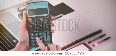 Hands of businesswoman using calculator against high angle view of documents and diary