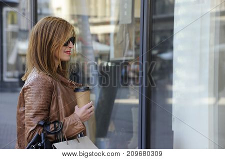 Trendy young hipster woman is looking through shop window, her face is reflecting. City style conception.