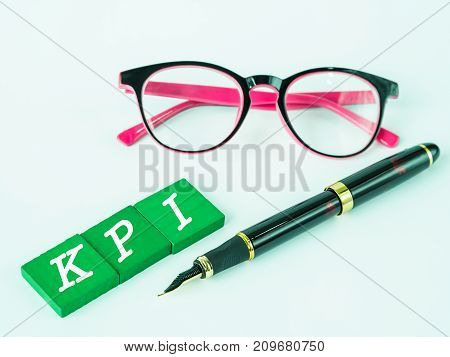 KPI alphabet with black pen and pink glasses on white table background.
