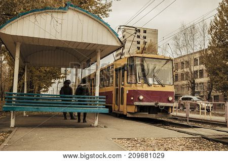 The old tram drove up to a stop in order to pick up passengers