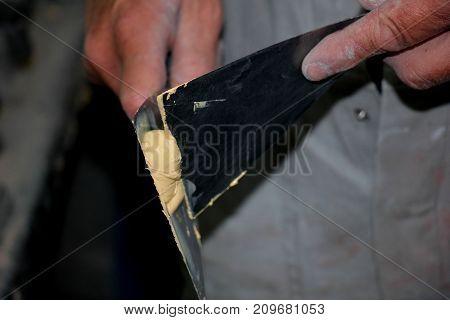 Man preparing filler in a vehicle repair shop