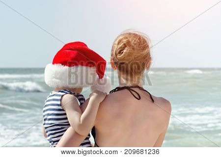 Kid In Santa Hat In The Arms Of Mother, The Beach. Back View