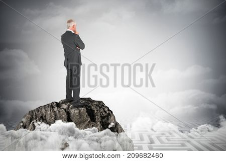Thoughtful businessman standing back to camera against maze ending in cloudy sky