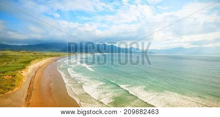 Idyllic view of waves in sea against cloudy sky