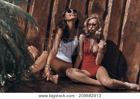Playful girls. Attractive young women in swimwear making her friend laugh by making a face while sitting against the wooden wall outdoors