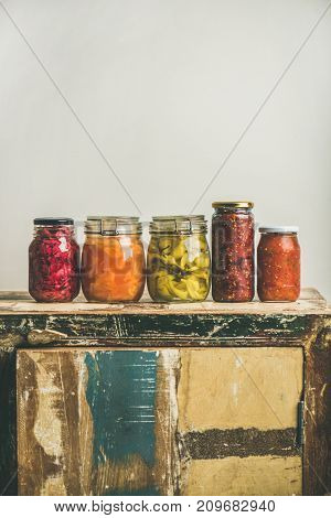 Autumn seasonal pickled or fermented vegetables in jars placed in line over vintage rustic kitchen drawer, white wall background, copy space. Fall home food preserving or canning