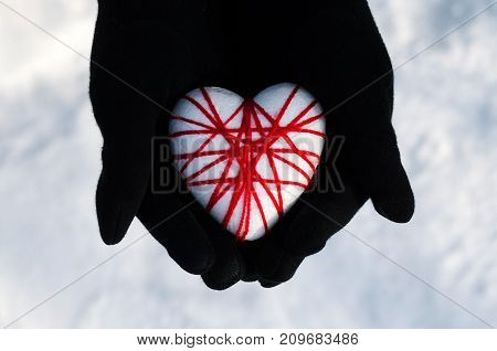 Woman Hands Holding The Heart On A Snowy Winter.