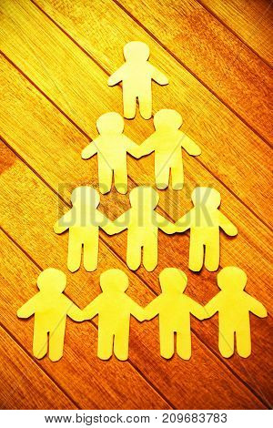 High angle view of paper cut out figures forming human pyramid on table
