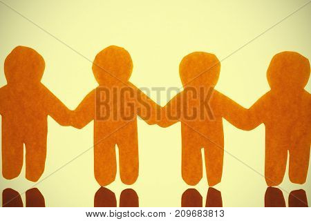 High angle view of yellow paper cut out human chain with reflection on glass table
