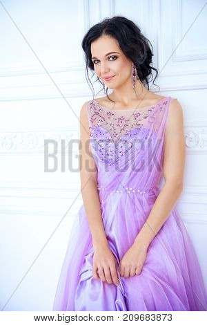 Portrait of a beautiful bride woman in a luxurious purple wedding dress. Makeup and hairstyle.