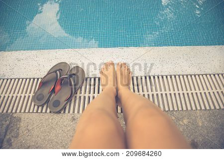 Man's feet with his colorful slippers beside the swimmingpool