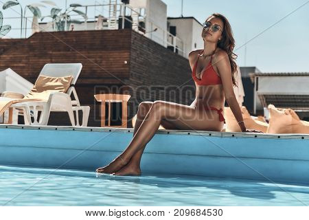 Enjoying summer vacation. Beautiful young woman in swimwear keeping eyes closed while sitting by the pool outdoors