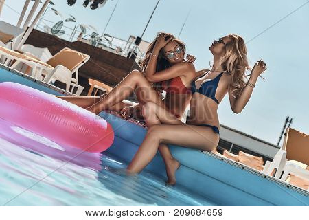 Poolside fun. Two beautiful young women in bikini smiling while sitting by the pool outdoors