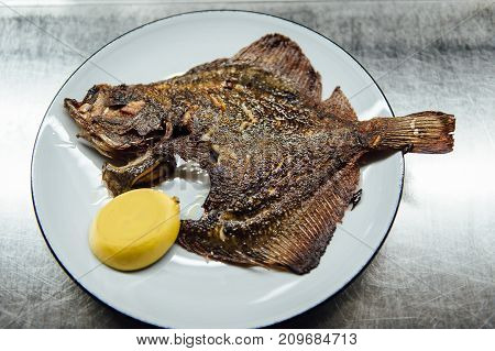 Fried Fish flounder on white plate with lemon on steel background